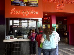 Movie-Goers wait to purchase tickets to a movie.